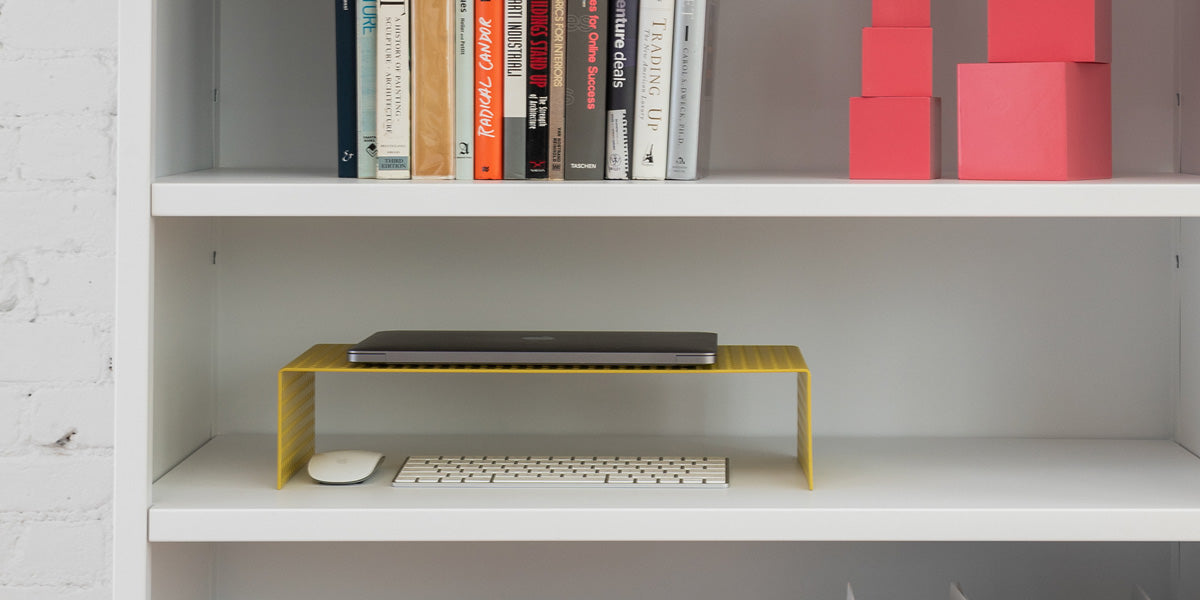 Heartwork Monitor Stand in yellow on shelf with laptop, keyboard and mouse