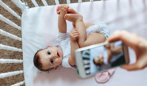 Taking a photo of a baby in crib with phone