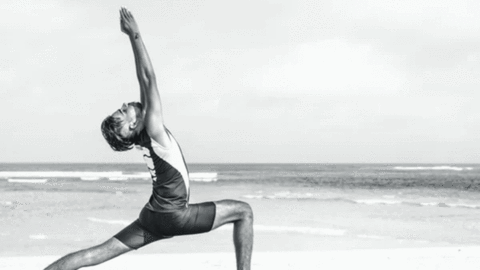A man performing the lunge pose near the see