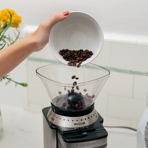 Image of coffee beans being poured into grinder