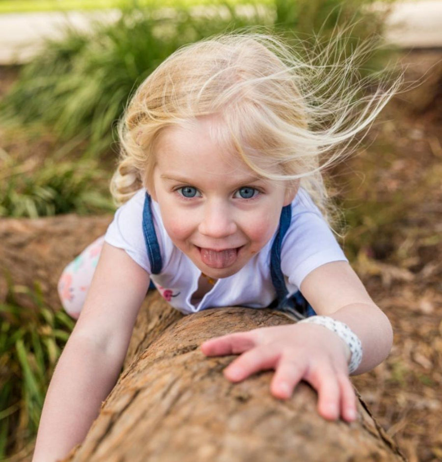 Young girl climbing tree with Patch coconut oil Patch strip on wrist