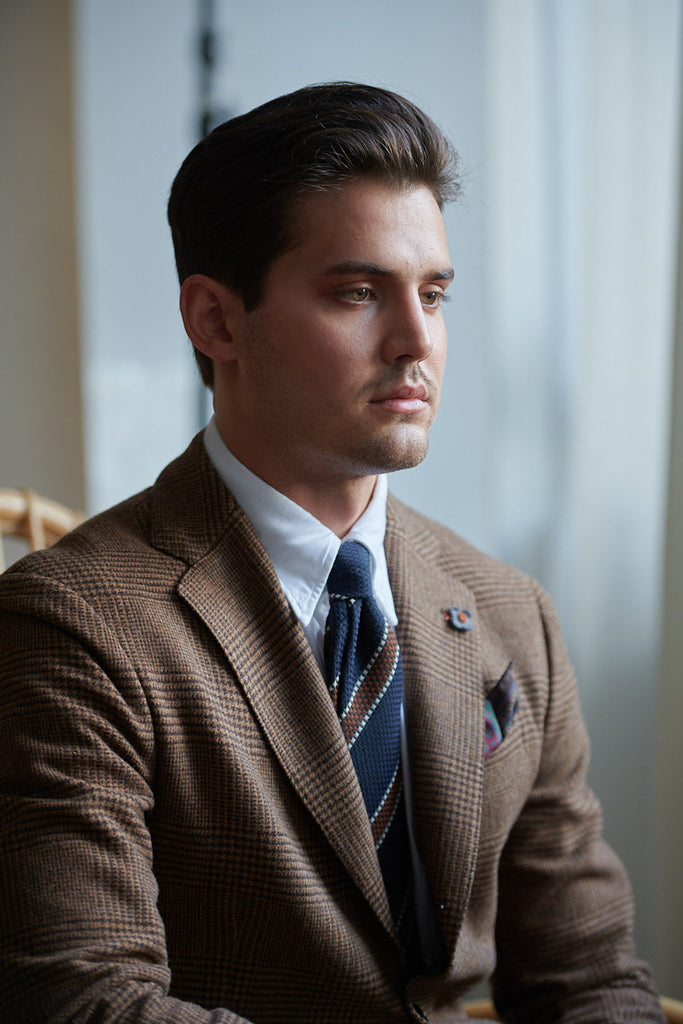 male model wearing blue white brown striped wool tie indoors