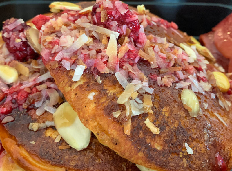 High Protein Pancakes featuring Redcon1 Birthday Cake Protein Powder with Caramelized Fresh Berry Compote and Toasted Coconut, Sugar Free Syrup and Turkey Bacon Served on the Side