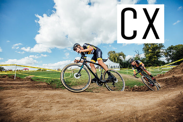 Two riders following each other on a dirt trail through a right hand corner on cyclocross bikes