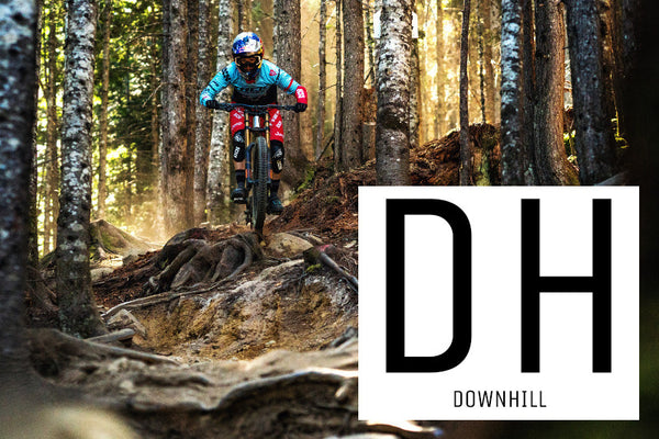 A girl riding a downhill mountain bike through a very rough section of tree roots in a forest