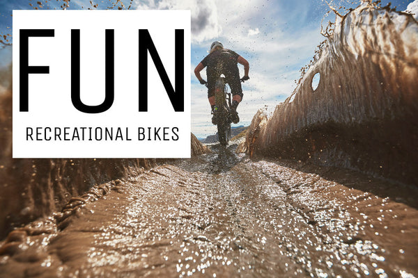 A rider creating a splash as they ride a recreational mountain bike through a puddle