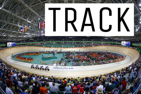 An image of a track teams pursuit team cycling around a velodrome with the crowd of spectators watching on.