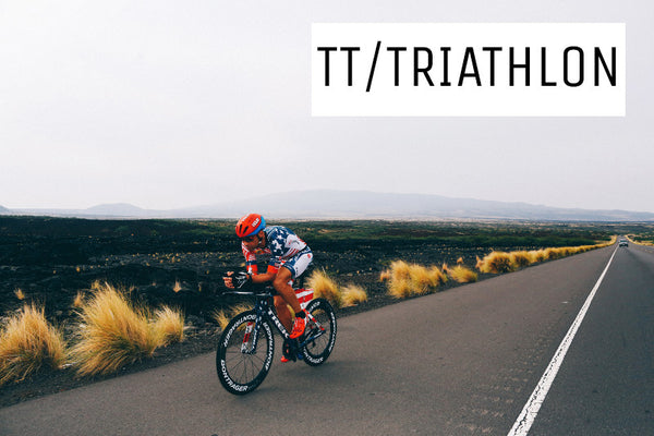 An image of a cyclist on a Trek speed concept triathon bike riding on a road passing through lava fields in Hawai.