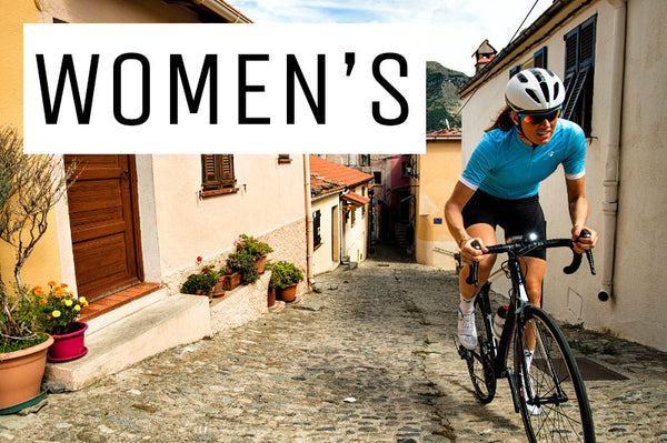 A girl riding on a women's specific road bike up a narrow cobbled street