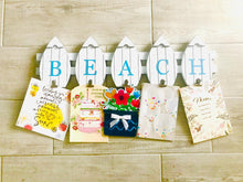 "Load image into Gallery viewer, White ""Beach"" Sign made with little White Surfboards and With Clips on the Bottom"