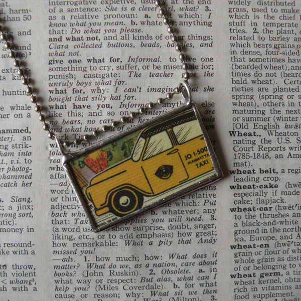 Vintage yellow taxi cab illustration, and vintage 1970s comic book onomatopoeia Tzing!, upcycled to hand-soldered glass pendant
