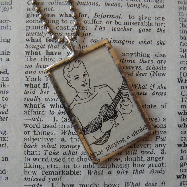 Boy playing ukulele, vintage dictionary illustration, hand-soldered glass pendant