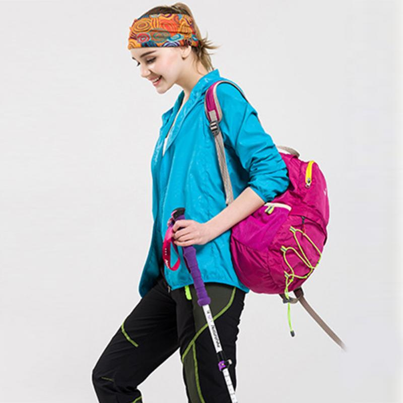 Lightweight waterproof jacket shown on female model with hiking gear