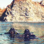 Divers shown in the sea using the wetsuit hood