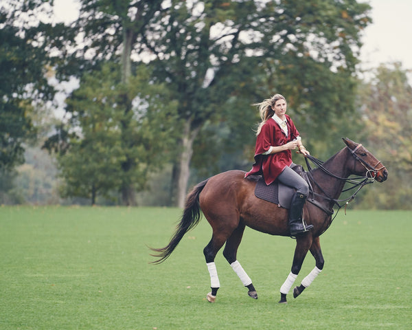 Woman riding a horse wearing an Alpaca Leather Trim Tassel Poncho in Burgundy - Stick & Ball