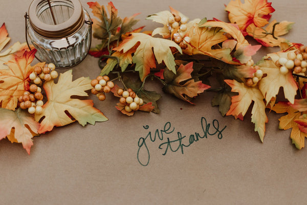 "table display of fall leaves and written out message, ""give thanks"""