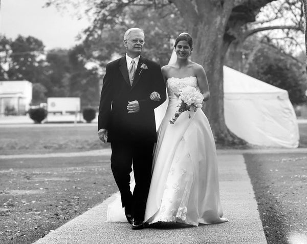 Black & White Photo of Stick & Ball founder, Elizabeth, on her wedding day walking down the isle with her father.