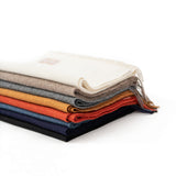 Stack of Luxury Alpaca Scarves in solid white, taupe, grey, mustard, coral, denim, navy and black
