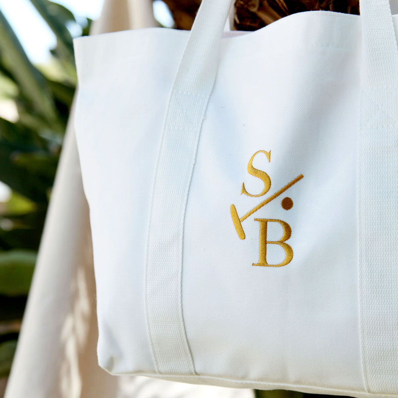 Cotton Canvas White Embroidered Tote with Stick & Ball Logo in Gold, hanging