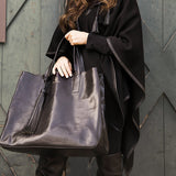 Woman holding vegetable-tanned Italian leather Wellington Weekender Tote - Black - Stick & Ball