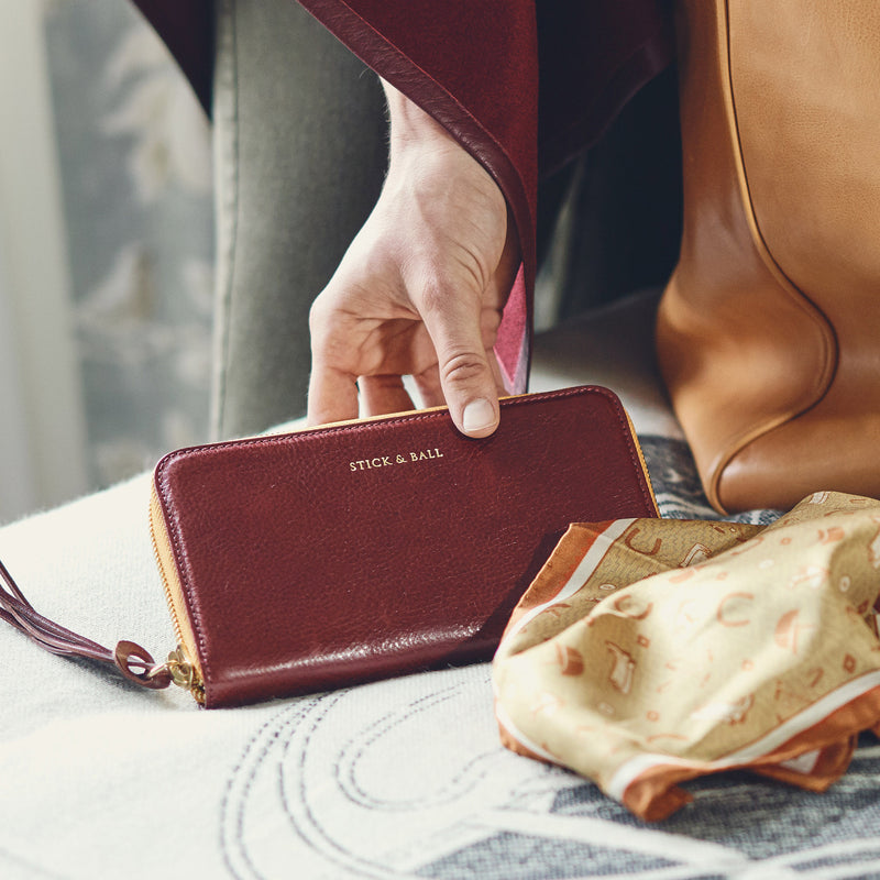 Woman holding Handmade Vegetable-tanned Italian Leather Zip/Clutch Wallet in Burgundy - Stick & Ball