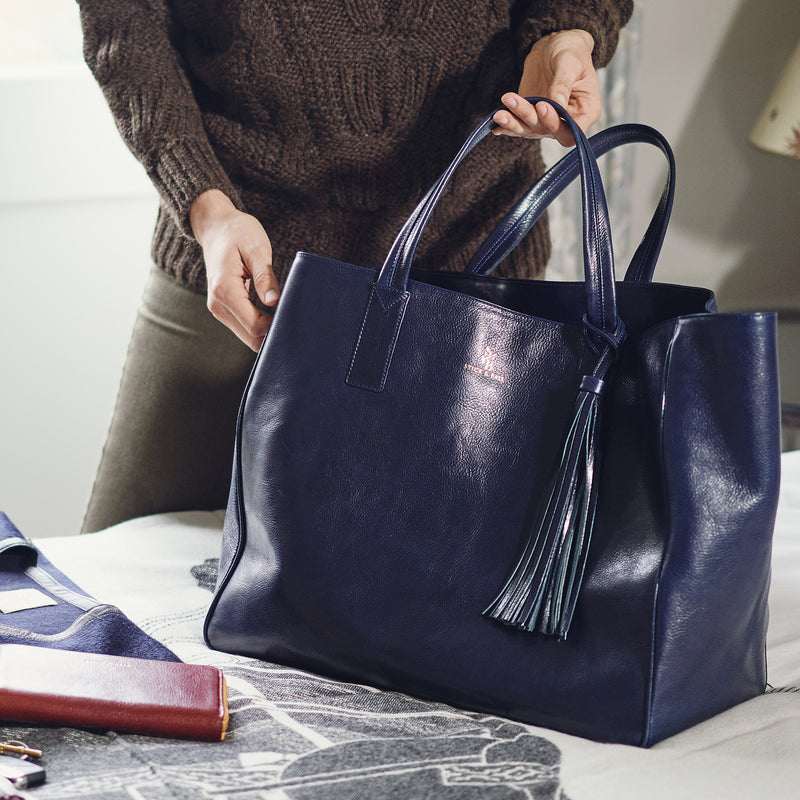 Woman holding vegetable-tanned Italian leather Wellington Weekender Tote - Navy - Stick & Ball