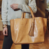 Woman holding vegetable-tanned Italian leather Wellington Weekender Tote - Tan - Stick & Ball