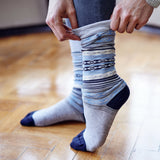 Woman putting on Pampa Boot Sock in Blue & Grey - Stick & Ball
