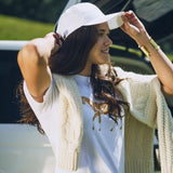 Woman wearing Embroidered Baseball Cap in White with Stick & Ball logo in Gold