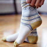 Woman putting on Pampa Boot Sock in Cream with cream & gold - Stick & Ball