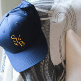 Embroidered Baseball Cap in Navy with Stick & Ball logo in Gold