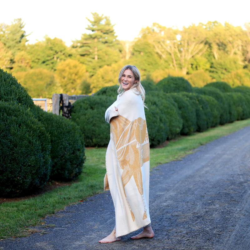 Woman wearing Jacquard-loomed Polo Pony Alpaca Throw Blanket - Gold - Stick & Ball