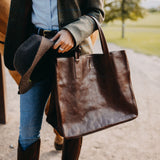 Woman holding vegetable-tanned Italian leather Wellington Weekender Tote - Brown - Stick & Ball
