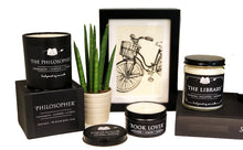 Load image into Gallery viewer, Three different candle options are shown, including a tumbler candle, a glass candle, and a candle in a tin. Each have monochrome coloring and are shown with decorative elements to highlight their versatility, including a drawing in a back frame and a plant in a white pot.