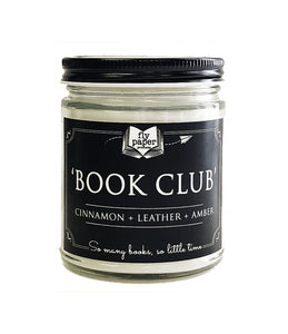 "A 9oz candle in a clear glass jar with black tin lid, called Book Club, which has notes of Cinnamon, leather, and amber indicated on a black label. Label reads ""So many books, so little time"", and includes Fly Paper Products logo."