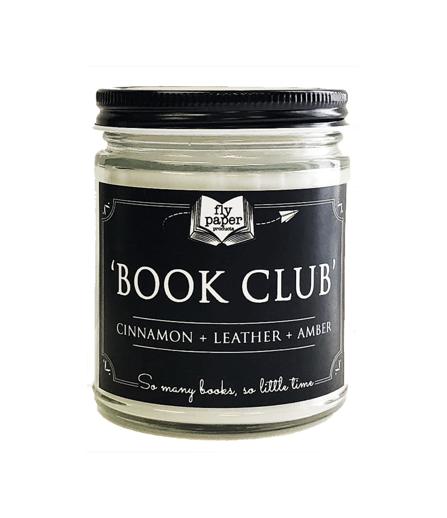 A 9oz candle in a clear glass jar with black tin lid, called Book Club, which has notes of Cinnamon, leather, and amber indicated on a black label. Label reads