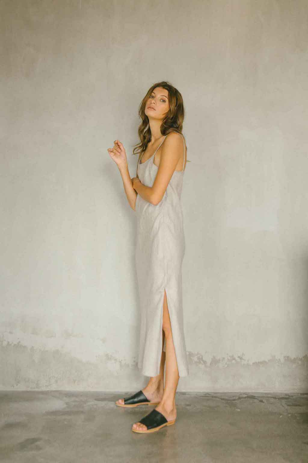A relaxed maxi dress made from 100% linen in natural color with high slit