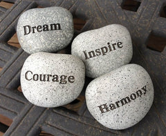 four smooth round stones engraved with the inspirational words, dream courage inspire and harmony