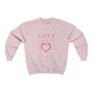 light pink super soft unisex crew neck sweatshirt with heart design and love matters slogan print