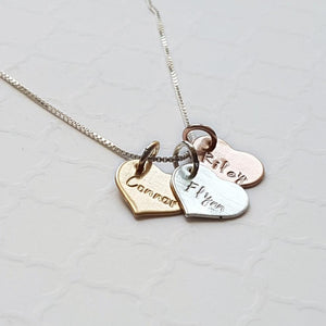 mixed metal name necklace with sterling silver, rose gold, and yellow gold hearts