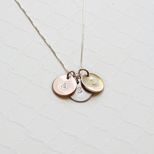 mixed metal necklace with initial discs in sterling silver, rose gold, and yellow gold