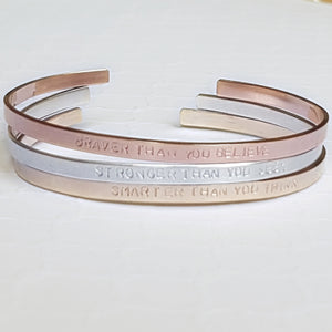 stack of cuff bracelets in sterling silver, rose gold and yellow gold