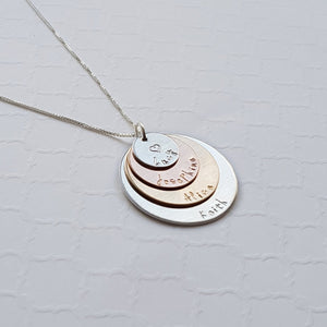 four-layer mixed metal necklace with sterling silver, rose gold, and yellow gold discs