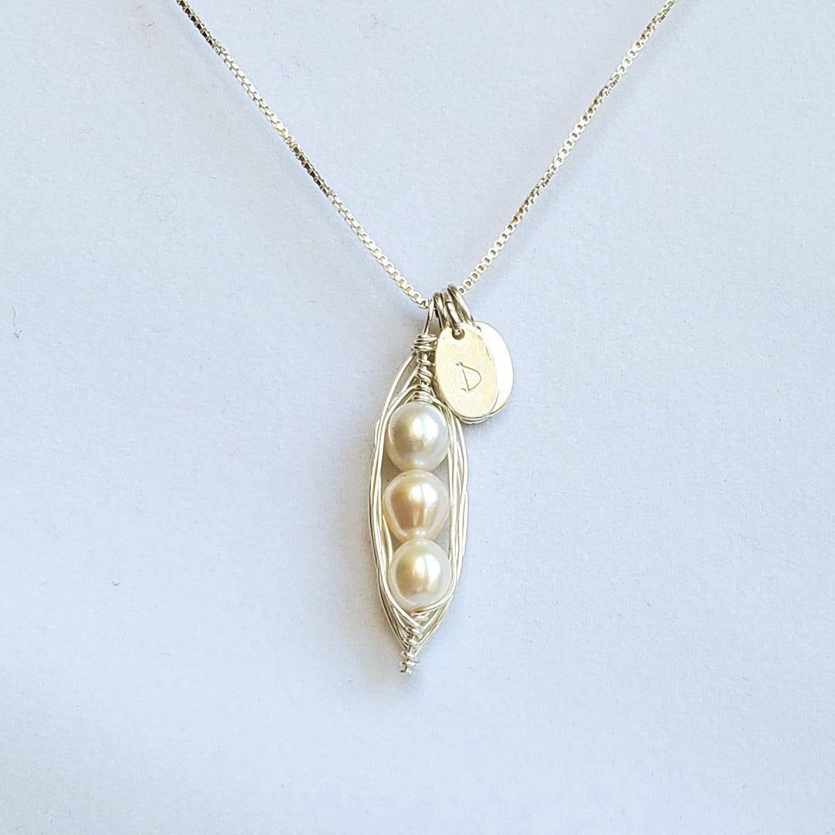 Wire-wrapped sterling silver pea pod necklace with freshwater pearls and initial charms