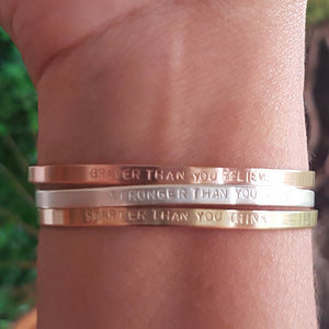 rose gold, yellow gold, and sterling silver cuff bracelets on a woman's wrist