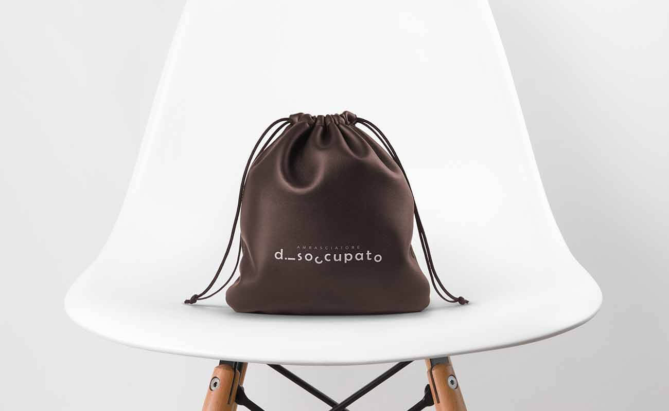 "a small bag on a chair, a writing on the bag says ""ambasciatore disoccupato"""