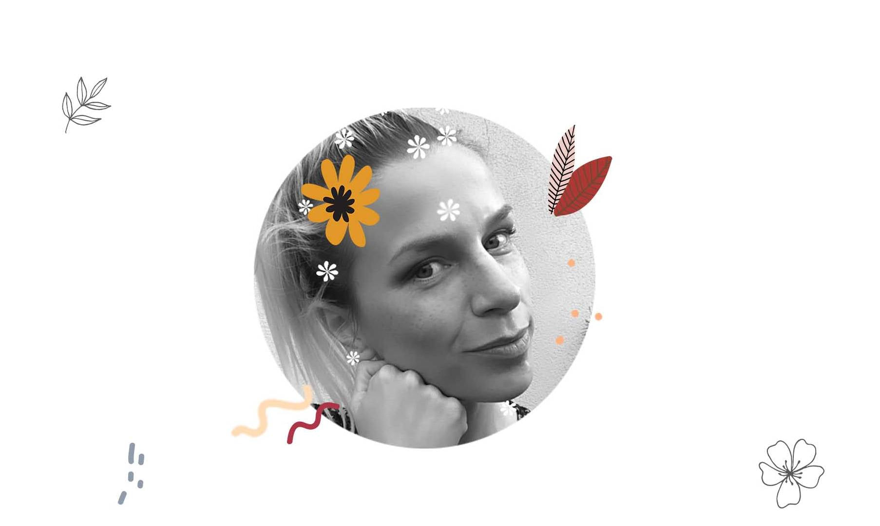 A round black and white image, a portrait of the illustrator Darka White. A woman with a pony tail, she's surrounded with some flowers.