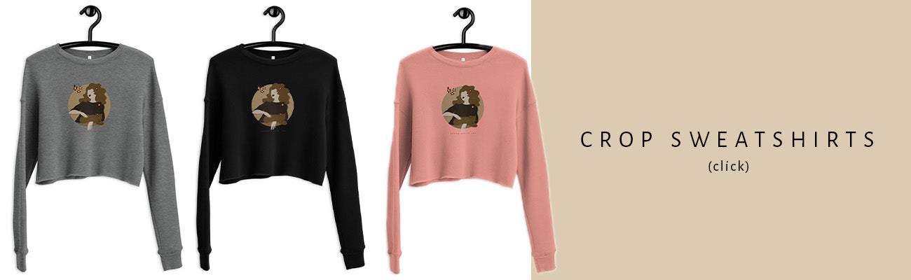 """Three crop sweatshirts of different colors. They all have the same illustration printed on the front side and they are all on hangers. On the right side of the image is a sign """"Crop Sweatshirts""""."""