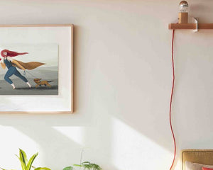 A wall with a framed illustration by Darka White. On the illustration is a girl with an apple in one hand and a dog on a leash in the other hand. Only a part of the frame can be seen. On the same wall is also a shelf with a lamp and a cable. At the bottom are some leaves of plants and a part of a bed.