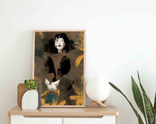 Load image into Gallery viewer, A framed illustrated artwork of a female portrait by Darka White. Frame is on a piece of furniture, next to it is a vase with a plant and a small circle lamp. In the right corner are leaves of another plant.